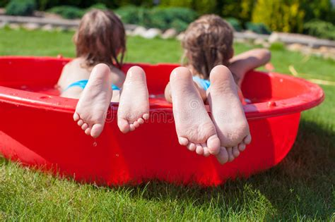 Close-up Of Feet Two Sisters In Small Pool Stock Image
